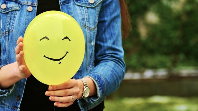 a woman holding a balloon with a smiley face