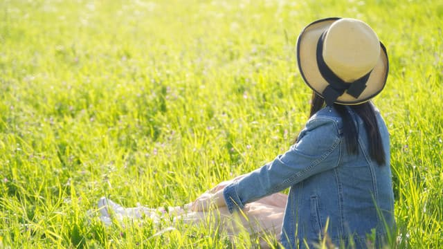 Girl sitting on the grass in the sun, enjoy the pleasure of living by God's words