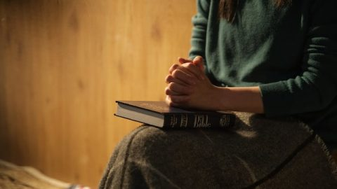 A Christian woman is praying and reading Bible